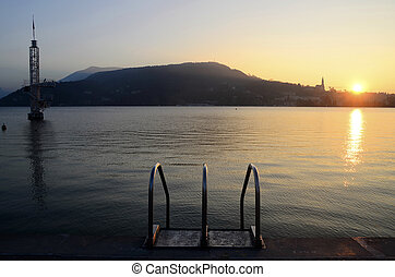 Sunset on Annecy city and diving structure on lake, Savoy,...