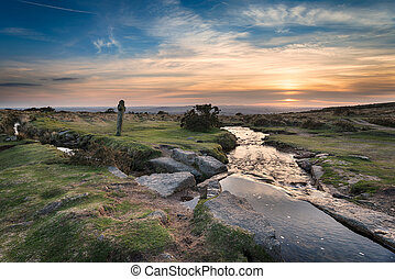 Sunset at Windy Post an ancient granite cross standing alongside the Beckamoor Brook as it crosses the Grimstone and Sortridge Leat near Moortown on Dartmoor