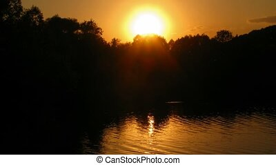 Sunset on lake: sun moves over trees, in the summer. Time...