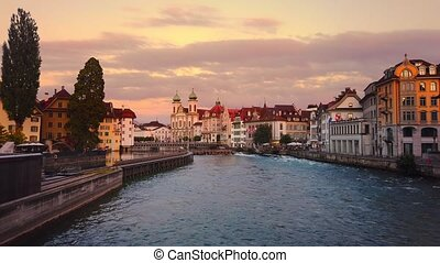 sunset on the city downtown of Lucerne of Lucerne river in central Switzerland. Jesuitenkirche or Jesuit Church of St. Francis Xavier on Reuss river. Famous landmark of historical Swiss city.