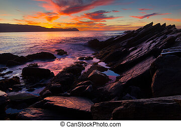 Sunset on ocean beach with rocks