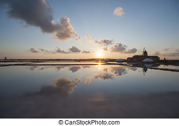 sunset on saltworks with old windmill in sicily, marsala,...