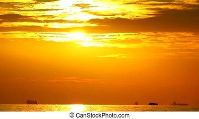 sunset on sea dark orange cloud moving and cargo ship