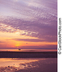 Sunset on sea during ebb with small fisherman boat on horizon
