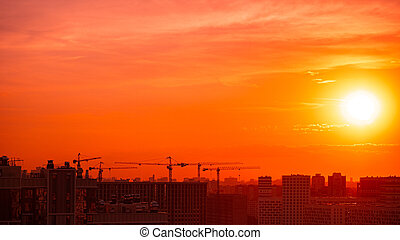 Sunset on the background of buildings under construction