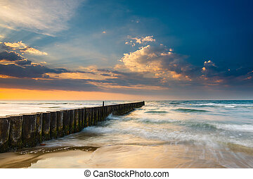 Sunset on the beach with breakwater, long time exposure