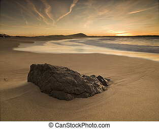 Sunset on the beach with rock in the foreground