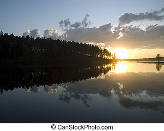 Sunset on the calm forest lake