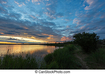 Sunset on the lake, with a path along the shore, a tree by the water and reeds in the foreground