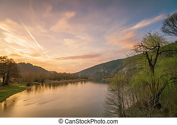 Sunset on the lake with forest with green grass