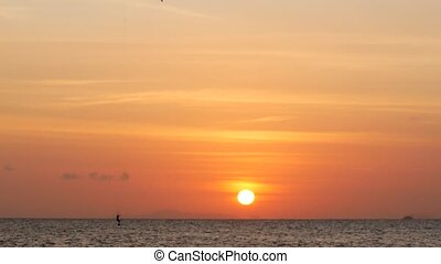 Sunset on the ocean, kite surfers ride on the sea