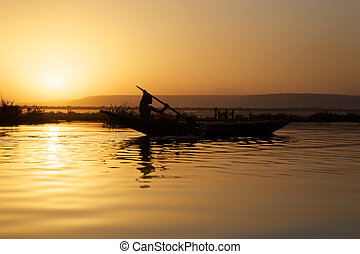 Local cruising on the river Niger in Bamako with sunset.