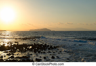 Sunset on the rocky beach in Mediterranean sea.