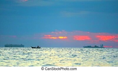 sunset on the sea and focus to fishing boat