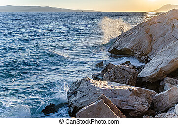 Sunset on the sea shore with rocks and pine forest.