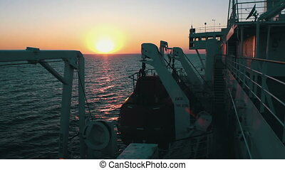 Sunset on the Sea with Moving Cargo Ferry.