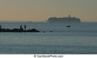 Sunset on the shore of the bay. Pair on the island. View of the ship entering the port