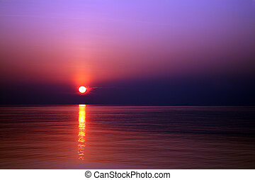 Sunset on the water - The setting sun fills the sky with...