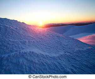 Sunset on top of snowy winter mountains on sky background