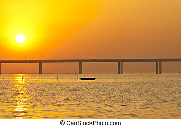 Sunset over a bridge with moving boats