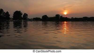 Sunset over a calm lake - Rippling water surface gleaming in...