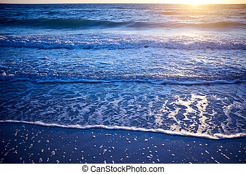 Sunset over a calm ocean with lapping waves
