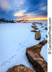 Sunset over a frozen lake - Beautiful sunset scene with a...