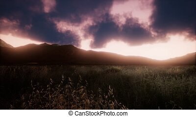Sunset over a green grassy rocky hills