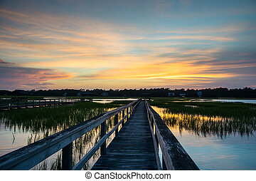 sunset over a long boardwalk and marsh at high tide