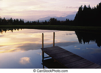Sunset over a pond and dock in Vermont