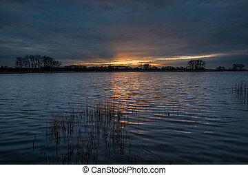 Sunset over a quiet lake and dark clouds in the evening
