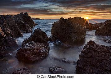 Sunset over a rocky beach in Australia
