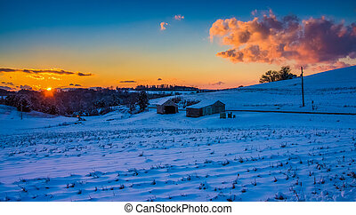Sunset over a snow covered farm field in rural York County, Pennsylvania.