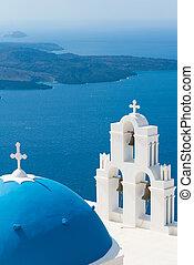 sunset over aegean sea with view to Virgin Mary Catholic Church Three Bells of Fira, Santorini, Greece.
