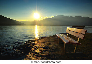 Sunset over an alpine lake with a bench and mountain