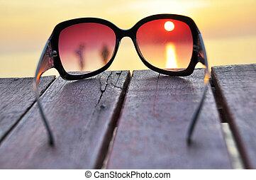 Sunset over an ocean through the sunglasses