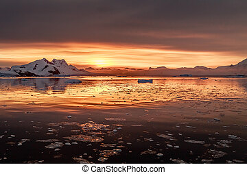 Sunset over antarctic lagoon with drifting icebergs and snow peaks in the background, Lemaire Channel, Antarctica