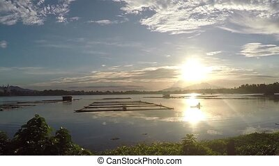 sunset over bamboo aquaculture structures in the middle of the lake. silhouettes