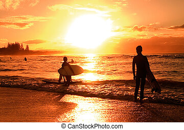 Sunset over beach - Kids with surfboards silhouetted against...