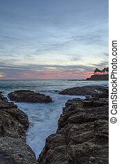 Sunset over beach rocks in Laguna