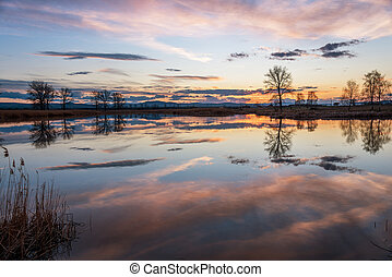Sunset over calm lake , sky reflection in water.