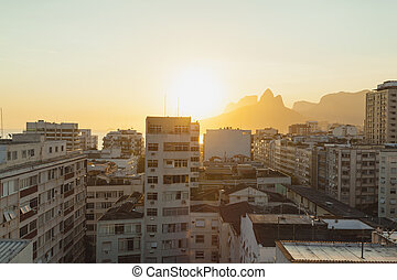 Sunset over city in Rio De Janeiro with buildings in...