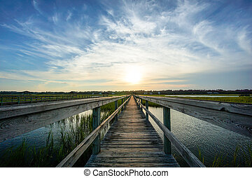 sunset over coastal waters with a very long wooden boardwalk