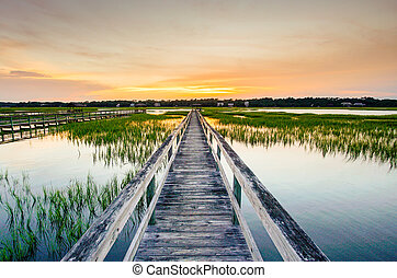 sunset over coastal waters with a very long wooden boardwalk pier in the center during a colorful summer sunset under an expressive sky with reflections in the water and marsh grass in the foreground
