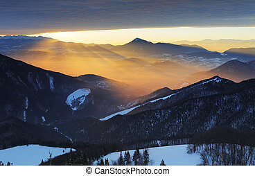 Sunset over color mountain silhouette with rays