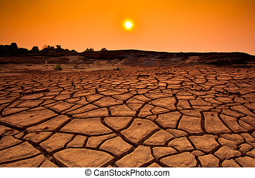 Sunset over cracked land and arid terrain