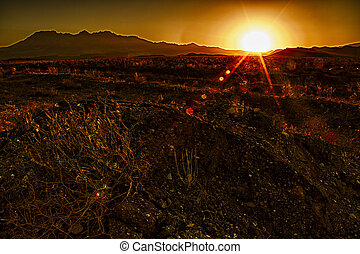 Sunset over desert - Sun setting over desert in early...