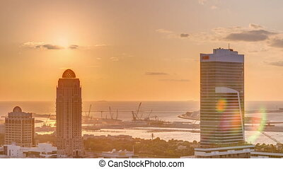 Sunset over Dubai Media City with Modern buildings aerial timelapse, United Arab Emirates. Palm Jumeirah on a background with traffic on a road