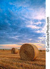 Sunset over farm field with hay bales in Hungary