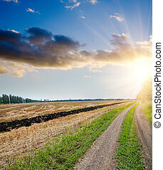 sunset over field and rural road with dramatic sky